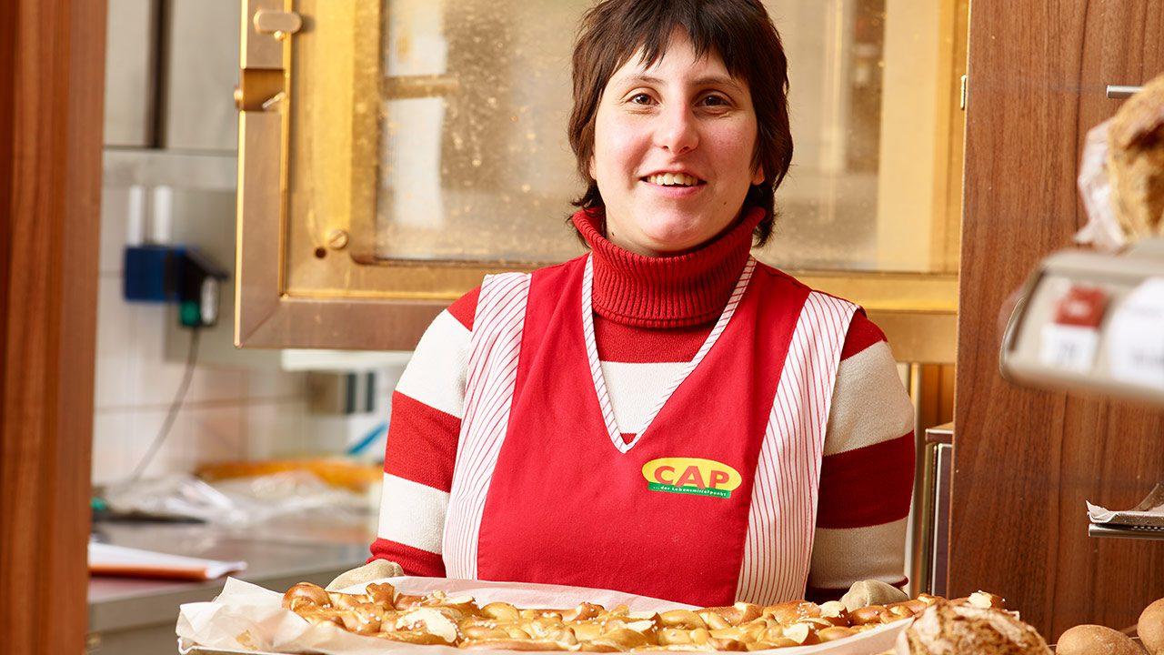 Bäckereigehilfin Alexandra Gradito präsentiert stolz lächelnd ein Blech mit Hefegebäck