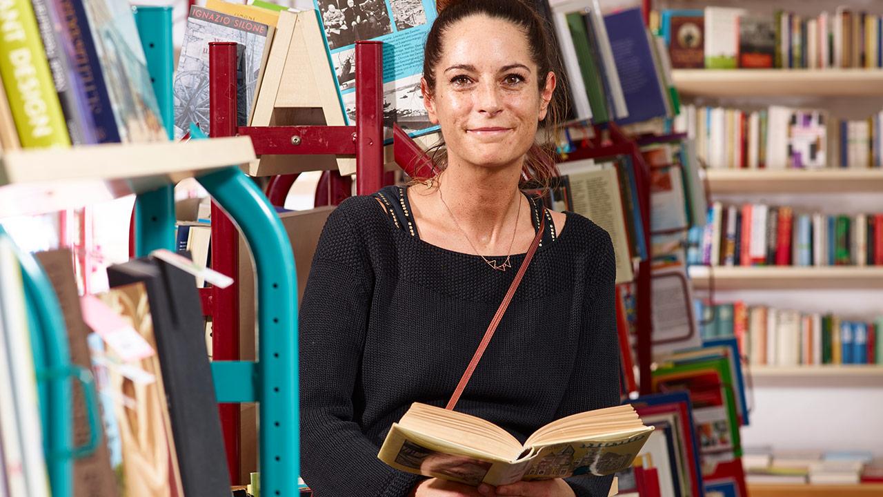 Buchhandelsassistentin Bianca Christ sitzt mit einem aufgeschlagenen Buch vor vollen Bücherregalen.