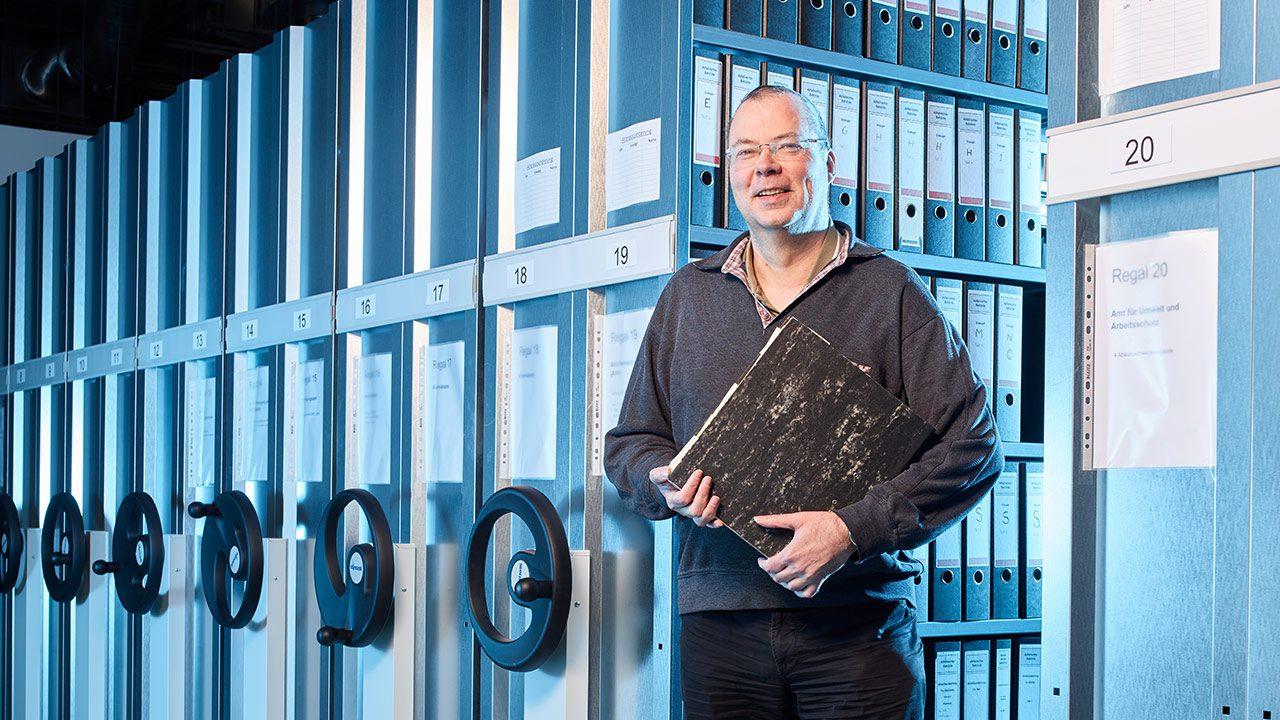 Archivmitarbeiter Gunther Heil steht mit einem Aktenordner vor einem riesigen Regalsystem.