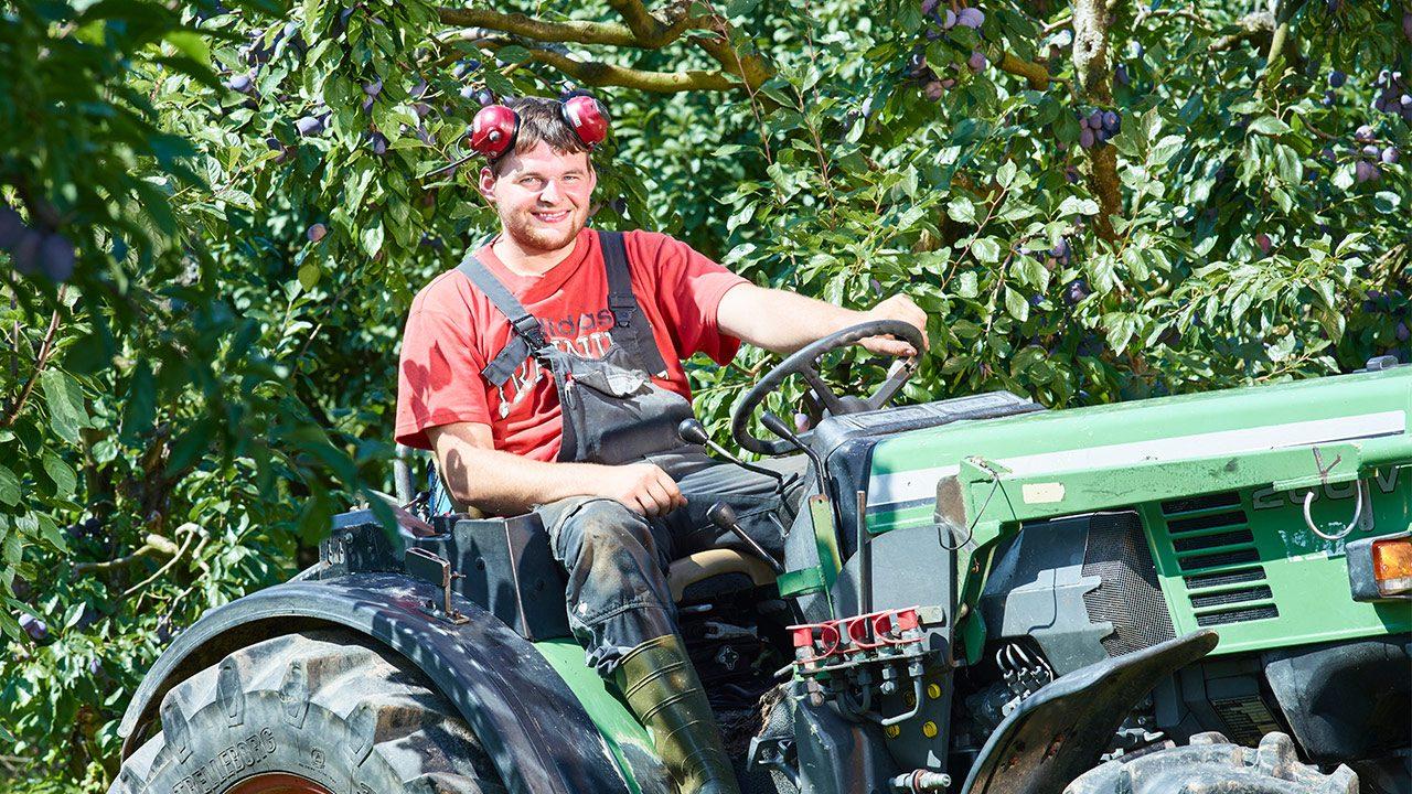 Landwirtschaftshelfer Michael Huber sitzt auf dem offenen Fahrersitz eines Traktors; auf der Stirn trägt er hochgeschobene Ohrenschützer.