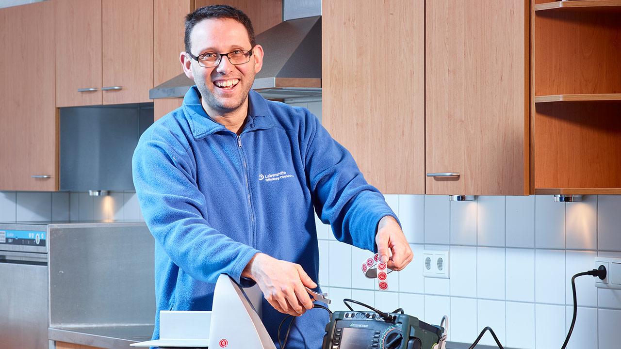 E-Geräteprüfer Stefan Erlach klebt lachend ein Prüfsiegel auf eine elektrische Brotschneidemaschine.