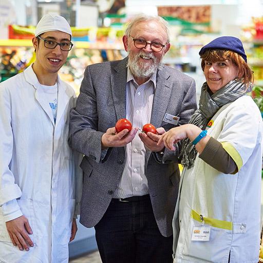 Eingerahmt von einem Mitarbeiter und einer Mitarbeiterin des Backshops, präsentiert der ehemalige BZKA-Geschäftsführer Willi Rast zwei Tomaten.
