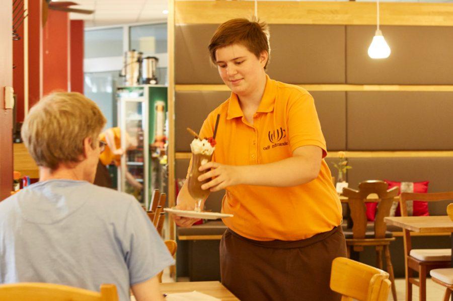 Tamara serviert dem Interviewer lächelnd einen Eiskaffee an einem Tisch im Innenraum des Cafés.