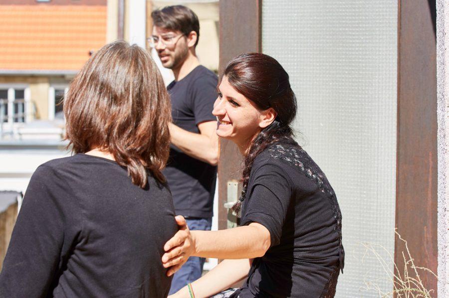 Yaprak sitzt mit Leon und einer weiteren Kollegin auf der Dachterrasse. Sie hat die Hand freundschaftlich auf den Rücken der Kollegin gelegt und lächelt sie an.