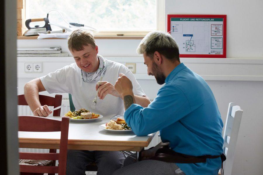 In einem Nebenraum der Küche nehmen Nico und Guiliano gut gelaunt ihr Mittagessen zu sich.
