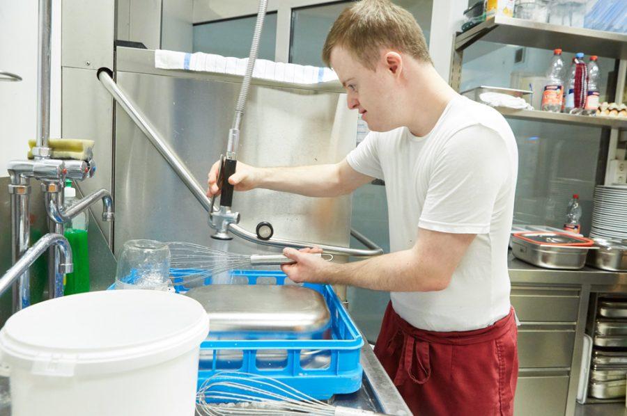 Der 27-jährige Florian spült in der Restaurantküche mit einer von der Decke hängenden Geschirrspülbrause einen Schneebesen ab.