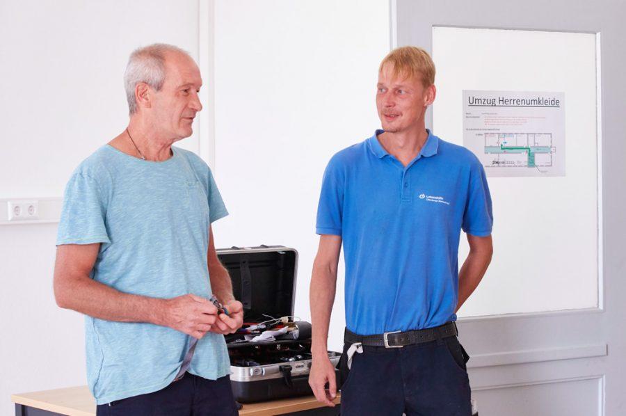 In einem frisch renovierten Raum unterhalten sich Anleiter Michael und Nico. Sie stehen dabei vor ihrem geöffneten Werkzeugkasten, der auf einem einfachen Arbeitstisch liegt.