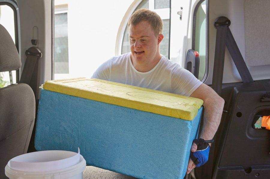 Florian hievt eine große Styropor-Warmhaltebox durch die seitliche Schiebetür eines Kleinbusses.