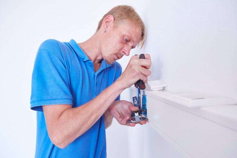 Großaufnahme von Nico, der mit einer Zange gerade den Anschluss einer Steckdose herstellt.
