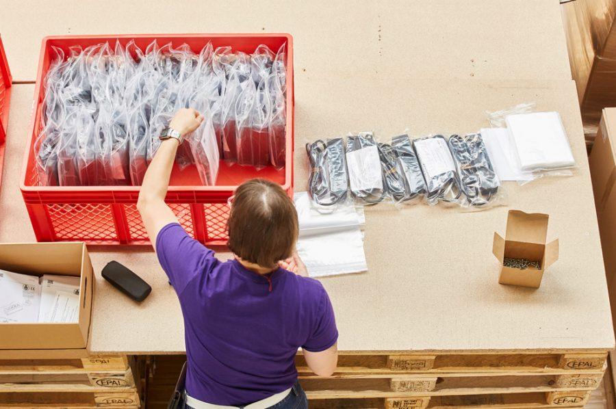 Hella sortiert die eingeschweißten Steckdosenleisten in einen großen roten Sammelkorb. Sie ist von hinten aus der Vogelperspektive aufgenommen.