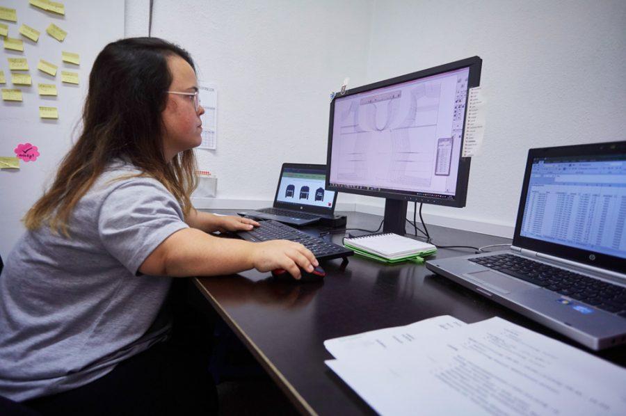 Nadine sitzt an einem großen schwarzen Schreibtisch und schaut konzentriert auf einen Flachbildschirm. Ein Laptop steht rechts, ein weiterer links von ihr.