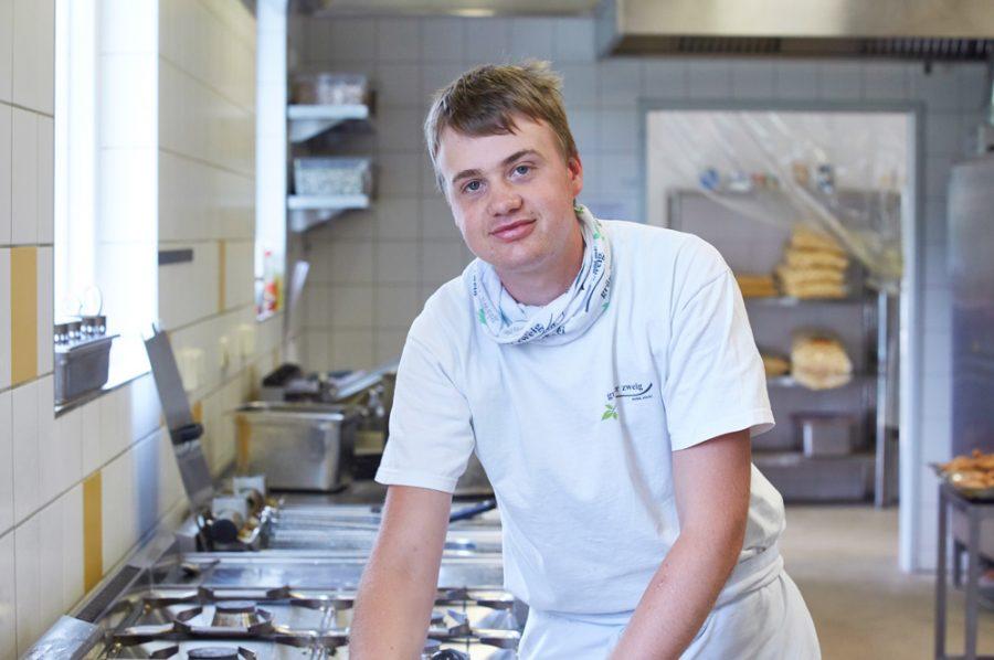 Großaufnahme vom lächelnden Nico, der sich in seiner weißen Küchenschürze leger auf die Spüle stützt.