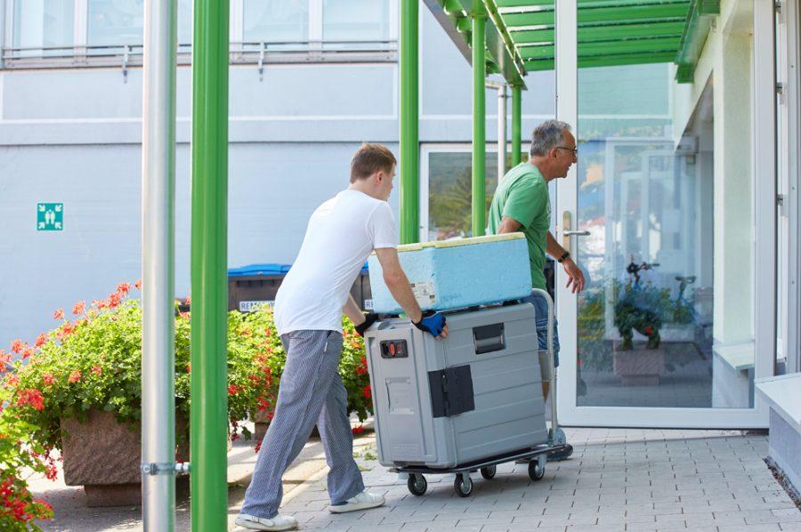Florian schiebt, sein Anleiter zieht einen Rollwagen mit den schweren Essenscontainern durch den Eingang des Kindergartens.