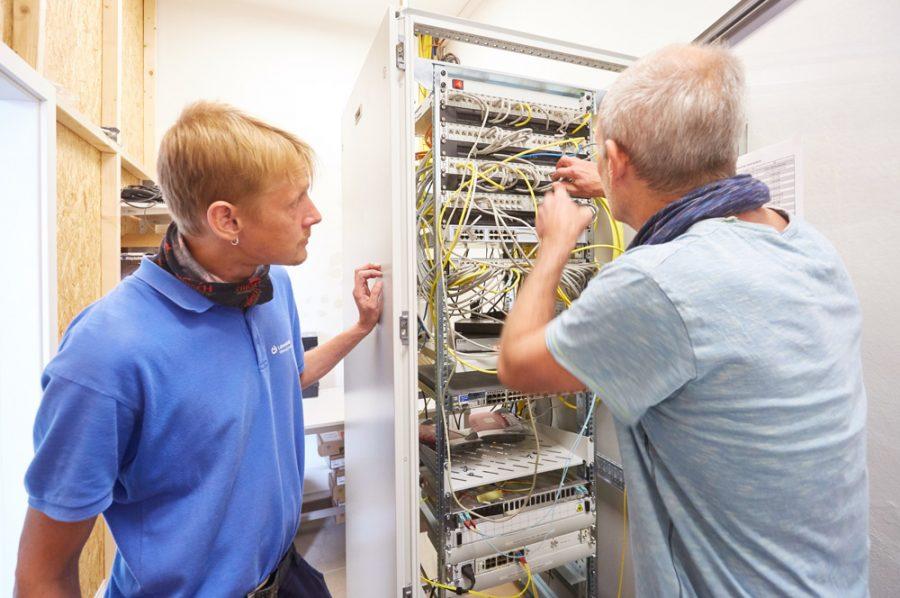 Michael prüft die Verkabelung in einem übermannshohen Serverschrank, Nico schaut ihm von der Seite zu.
