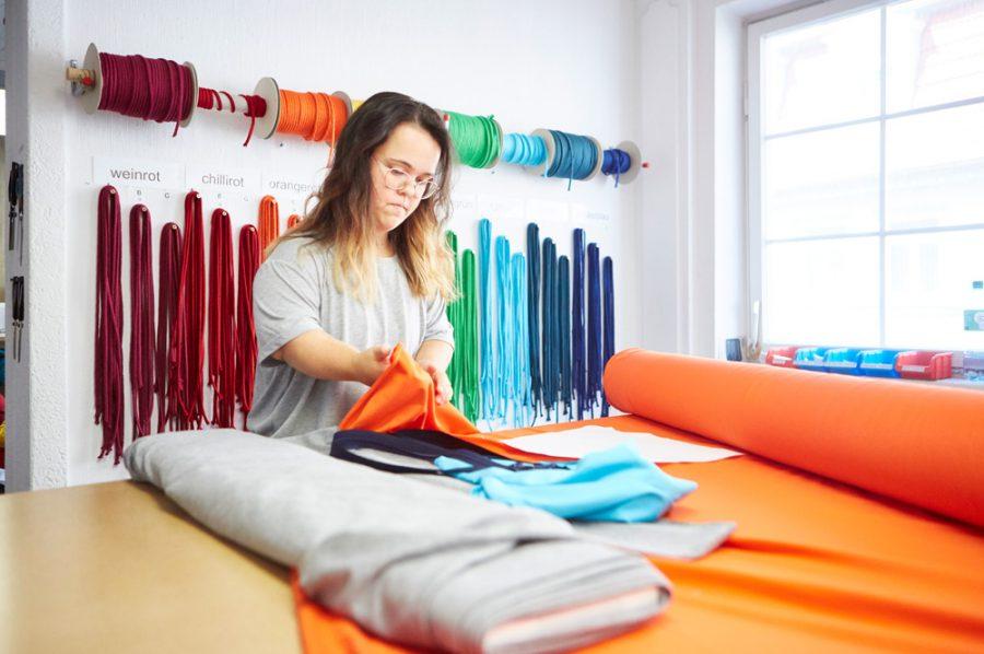 Nadine lässt am Schneidetisch ein orangefarbenes Stück Stoff durch die Finger gleiten. An der Wand hinter ihr hängen Spulen mit Kordeln in allen Farben, darunter kürzere Bänder an Nägeln.