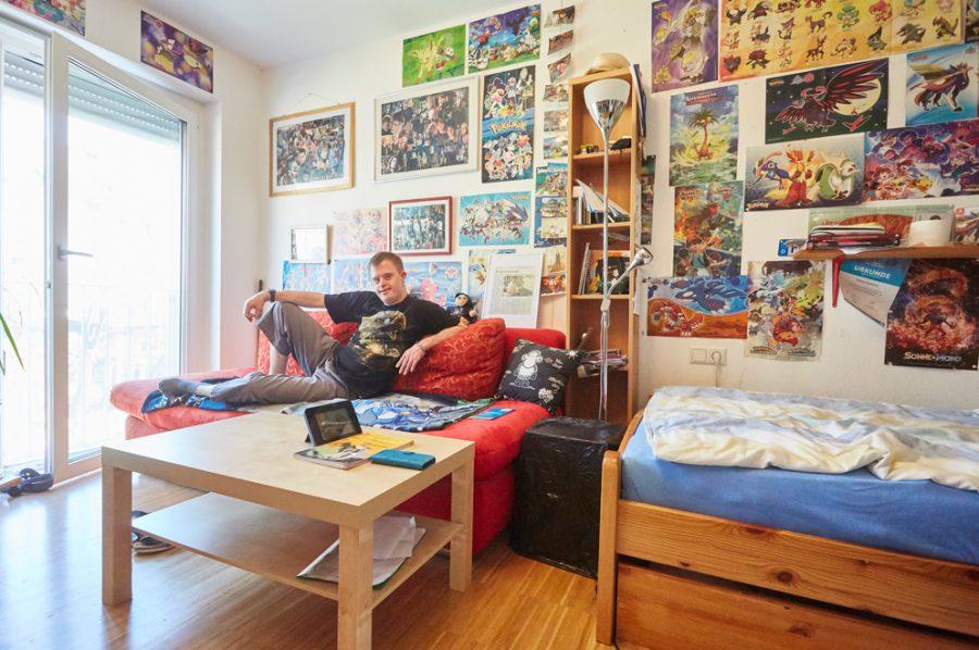 Florian fläzt sich entspannt auf dem roten Sofa in seinem WG-Zimmer. Viel Licht strömt durch das deckenhohe Fenster ein, die Wand hinter Florian ist mit Fantasy-Bildern geschmückt. Rechts ist ein Kieferbett mit Bettkasten zu sehen, vor dem Sofa ein quadratischer Couchtisch aus hellem Holzimitat.