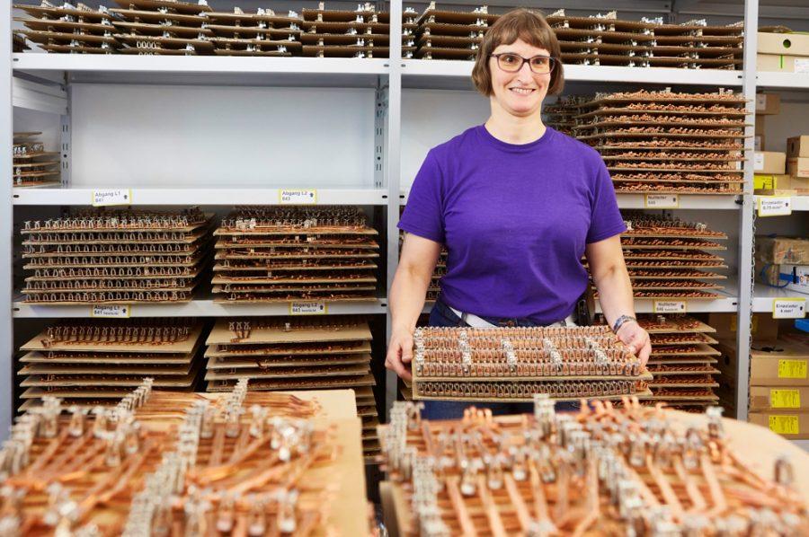 Hella hält einen Stapel mit Platten vor sich, auf denen kupferfarbene, längliche Metallstücke aufgereiht sind. Die Regale im Hintergrund sind gefüllt mit ebensolchen Platten.