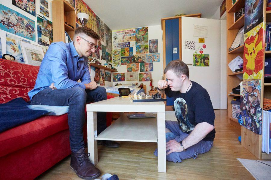 Florian und sein Begleiter von der Lebenshilfe beim Schachspiel. Der Begleiter sitzt auf dem roten Sofa, Florian auf dem Boden vor dem Couchtisch.
