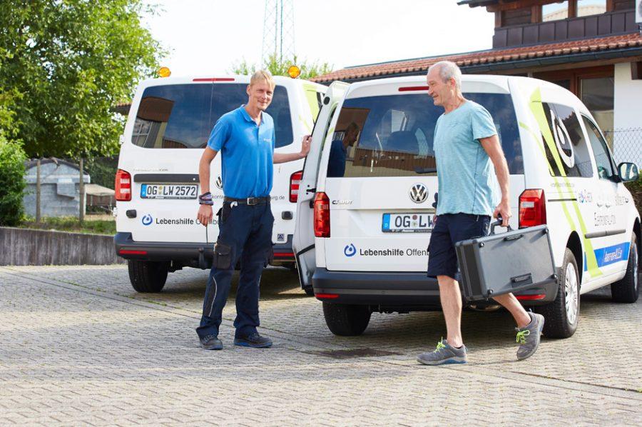 Nico und Michael vor dem Hochdachkombi der Lebenshilfe. Michael ist in der Vorwärtsbewegung und trägt den Werkzeugkoffer. Daneben sieht man ein weiteres Servicefahrzeug.