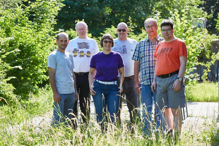 Hella inmitten einer Gruppe von fünf männlichen Kollegen. Die Terrasse, auf der die fröhliche Gruppe steht, ist umsäumt von grünen Büschen.