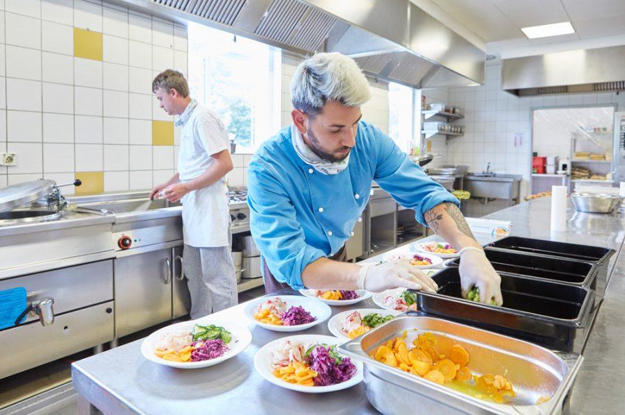 Auf der Arbeitsfläche richtet Guiliano bunte Salatteller an. Im Hintergrund spritzt Nico das Spülbecken aus.