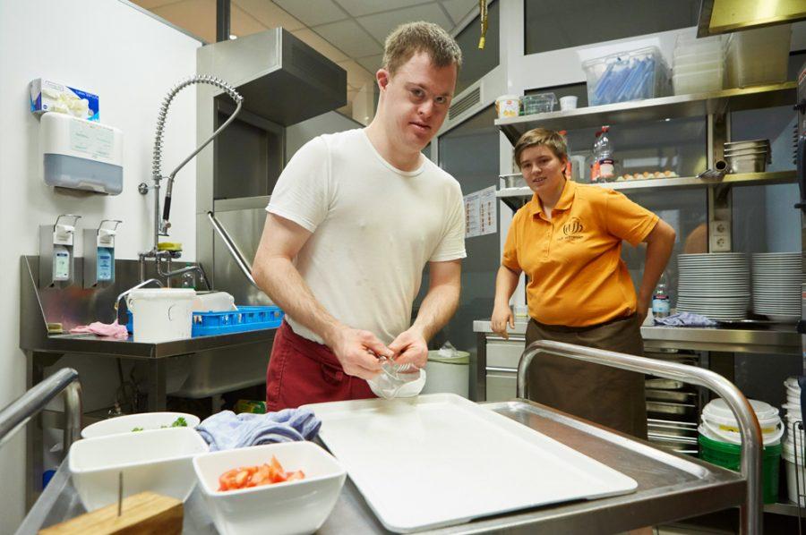Florian und Tamara in der Küche. Florian steht hinter einem Edelstahl-Servierwagen, Tamara lehnt im Hintergrund an einer Arbeitsfläche mit Tellerstapeln.
