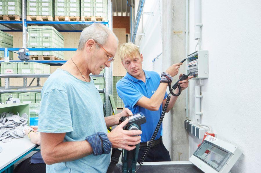 Nico prüft einen Sicherungskasten mit Hilfe zweier Sonden. Er schaut fragend zu Michael, der das Ergebnis am elektronischen Steuergerät abliest.