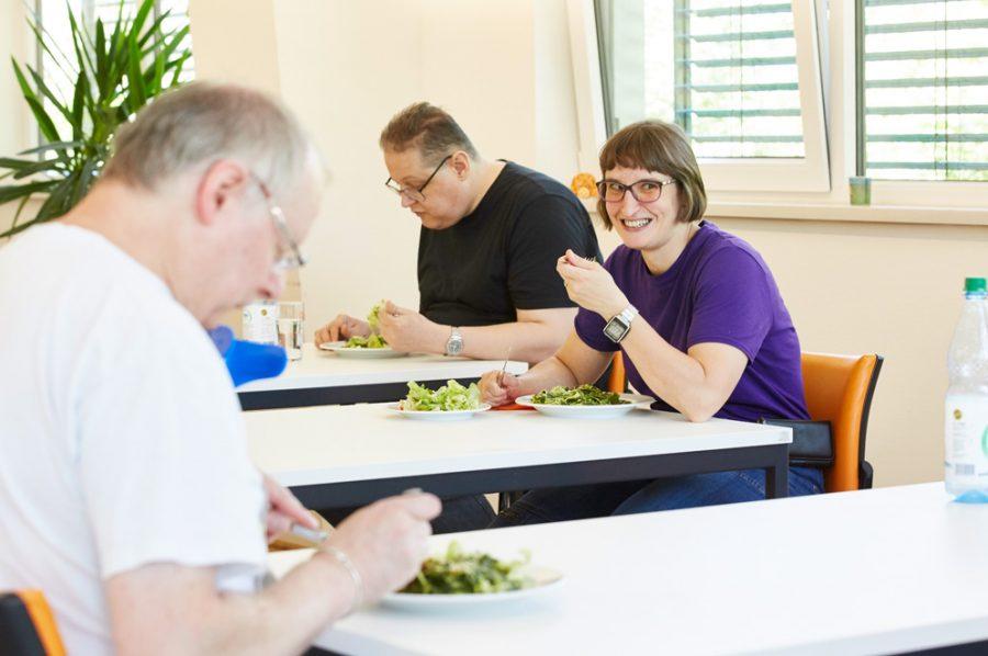 Hella und zwei Kollegen an getrennten Tischen beim Mittagessen. Die Tische stehen in großem Corona-Abstand zueinander. Links im Vordergrund sitzt der ältere Kollege, mit dem Hella sich besonders gut versteht.