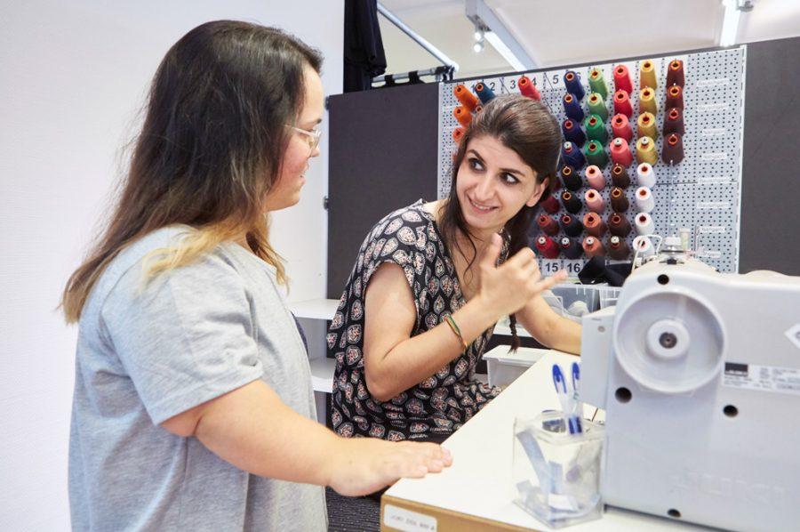 Die an der Nähmaschine sitzende Yaprak spricht mit Nadine, die neben ihr steht und aufmerksam zuhört. Yapraks ausdrucksvolle Gestik und Mimik prägen die Szene.