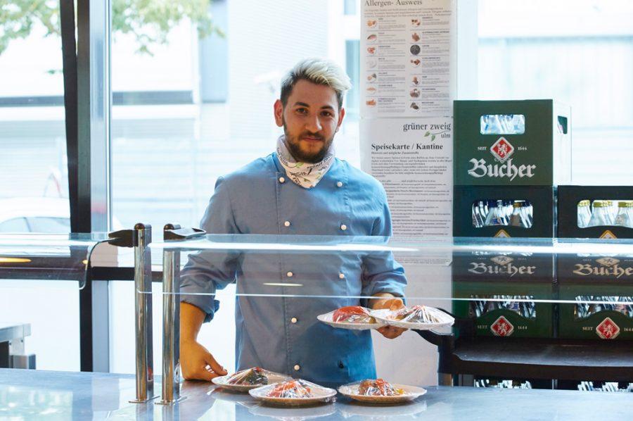 Guiliano im blauen Koch-Outfit steht hinter einer Kühlvitrine und hält zwei folierte Vorspeisenteller in einer Hand; weitere servierfertige Teller stehen auf der Theke vor ihm.