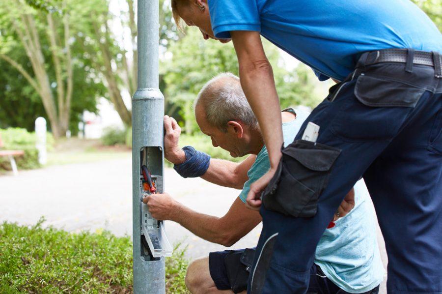 Vor dem geöffneten Sicherungskasten im Sockel einer Straßenlaterne kniet Michael, Nico schaut ihm über die Schulter.
