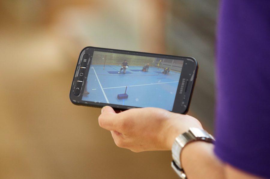 Eine Hand hält ein Handy, dessen Display die Mannschaftsaufstellung beim Torball zeigt.