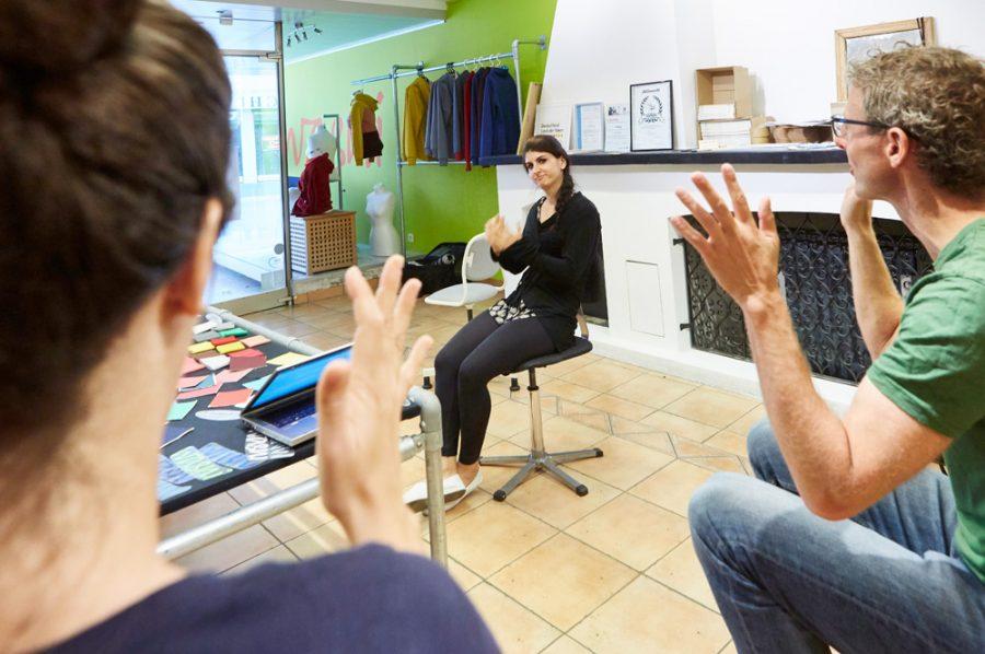 Yaprak, Daniel und die Gebärdendolmetscherin in einer Besprechung. Bei allen dreien sind die Hände in der Momentaufnahme des Gebärdendialogs nach oben gereckt, die Finger gespreizt.