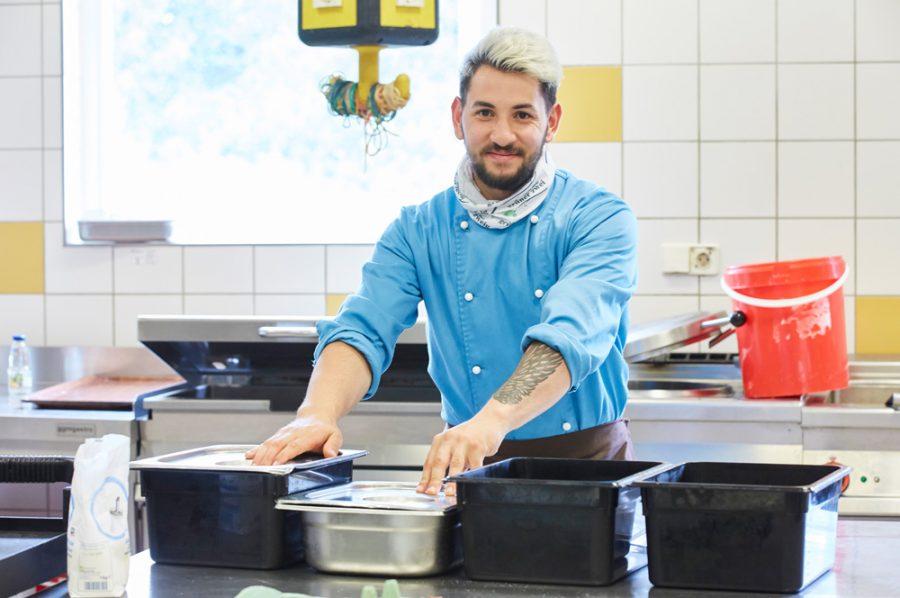 Guiliano legt die Hände auf die Deckel von zwei verschlossenen Edelstahlbehältern.