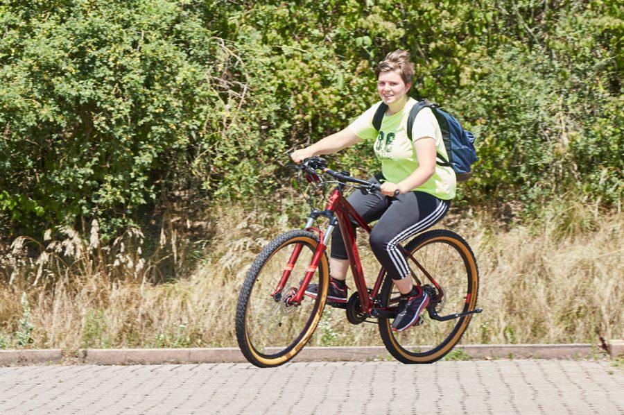 Tamara in voller Fahrt auf ihrem roten Mountainbike. Lächelnd genießt sie die Schräglage ihres Fahrrads. Im Hintergrund grünes Buschwerk.
