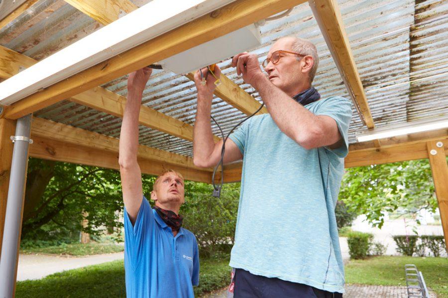 Michael prüft den Sicherungskasten unter einem halbtransparenten Kunststoffvordach. Der neben ihm stehende Nico greift nach oben, um eine Kabelverbindung zu checken.