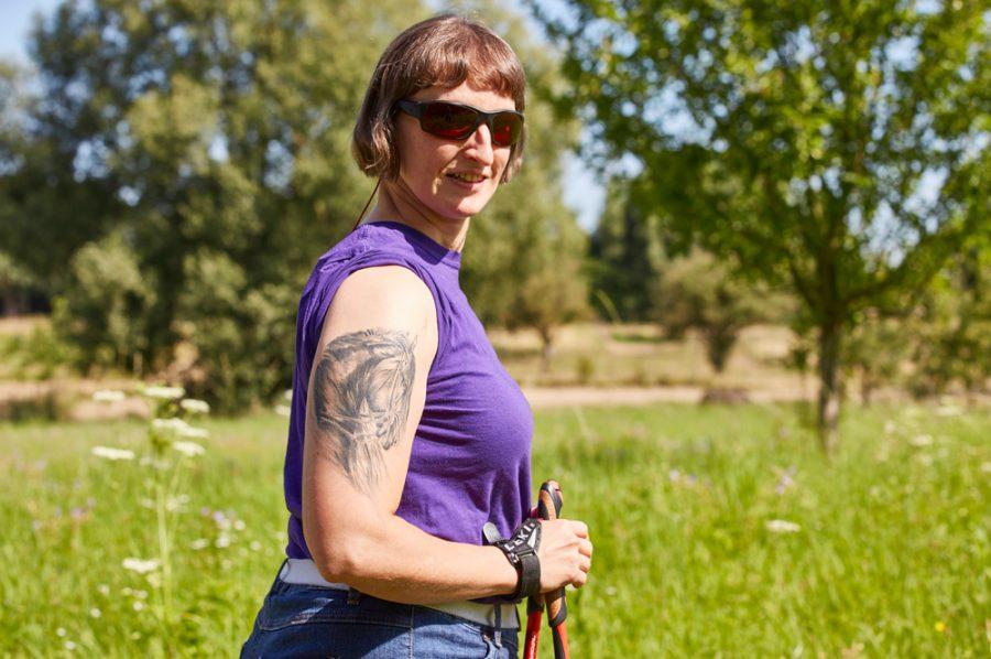Hella mit Walking-Stöcken und Sonnenbrille vor einer grünen Wiese. Auf dem rechten Oberarm sieht man das äußerst fein gestochene Tattoo eines Pferdekopfes.
