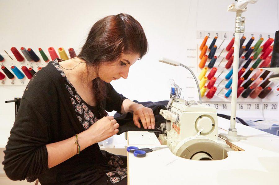 Yaprak von der Seite an der Nähmaschine. Sie zieht gerade sehr konzentriert ein schwarzes Stück Stoff unter der ratternden Nadel durch. Im Hintergrund sieht man an der Wand ein Farbenmeer an Garnspulen.