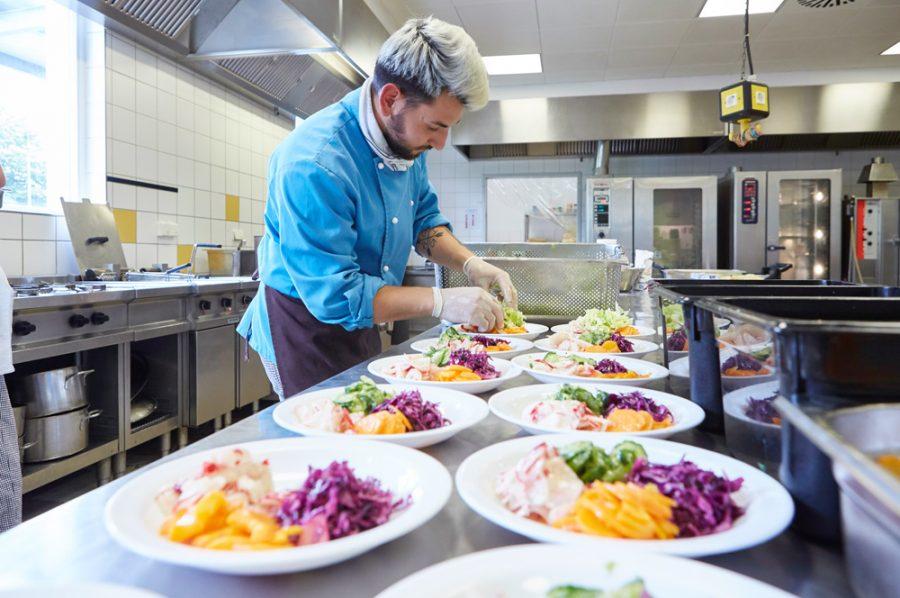 Guiliano rundet eine Salatmischung in einer langen Reihe von beinahe fertig angerichteten Salattellern ab. Aus dem Geschirr leuchtet es lila, gelb, grün und rosé.