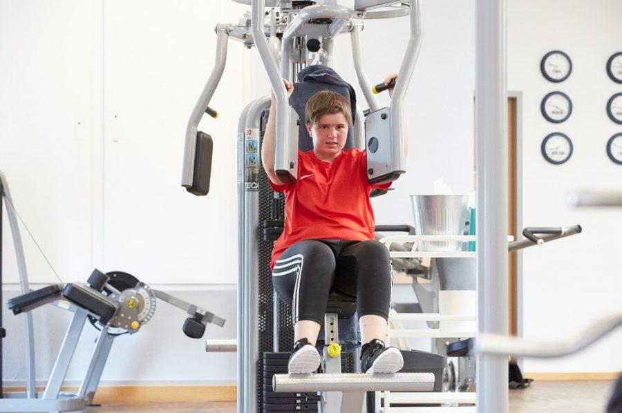 Tamara im Fitnessstudio. Sie sitzt auf einem grau und schwarz gehaltenen Hightech-Trainingsgerät, bei dem zwei Platten mit den Armen gegeneinanderzudrücken sind. Ihr Gesicht verrät die Anstrengung.