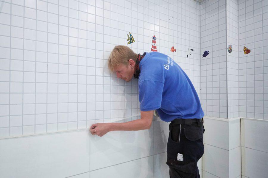 In einem weiß gekachelten Badezimmer klebt Nico mit Kreppband die Ränder der Kacheln ab, um die Silikonversiegelung der Fugen vorzubereiten.