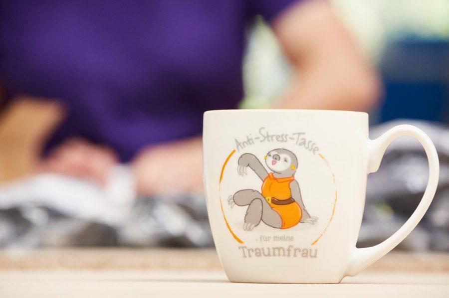 """Großaufnahme einer Bürotasse mit der Aufschrift: """"Anti-Stress-Tasse für meine Traumfrau"""". Das Bild dazu zeigt eine attraktive, entspannte Maulwurfdame im gelben Kleid."""