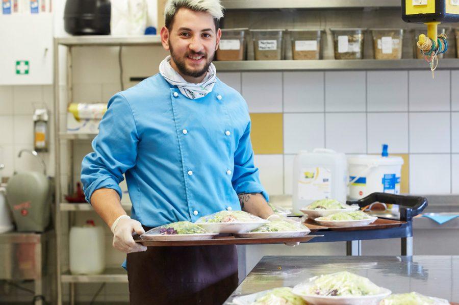 Guiliano trägt strahlend ein Tablett mit 3 großen folierten Salattellern vor dem Bauch.