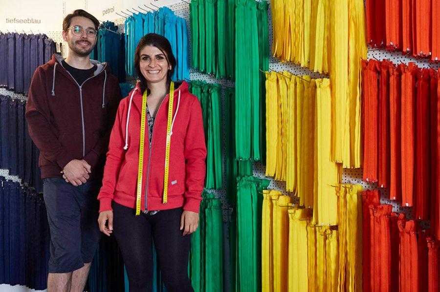Die strahlende Yaprak steht mit dem Kollegen Leon vor frei hängenden, langen Reißverschlüssen in allen Farben des Regenbogens.